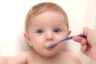 A baby with a colour changing spoon
